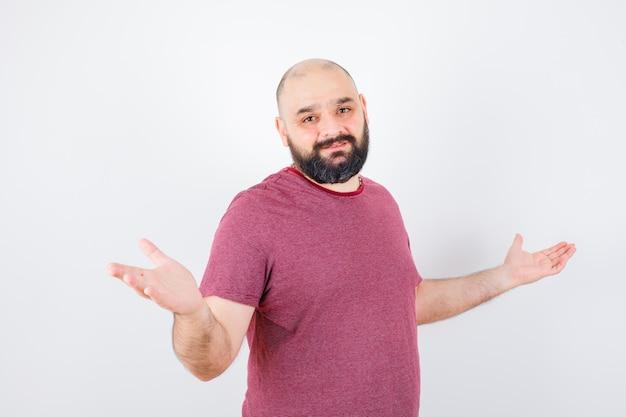 Jeune homme en t-shirt rose montrant un geste impuissant et l'air paresseux.