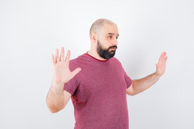 Jeune homme en t-shirt rose montrant un geste de reddition.