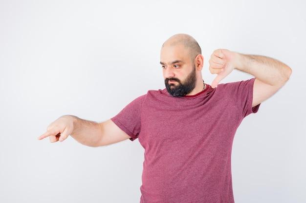 Jeune homme en t-shirt rose montrant le pouce vers le bas tout en pointant de côté et l'air nerveux, vue de face.