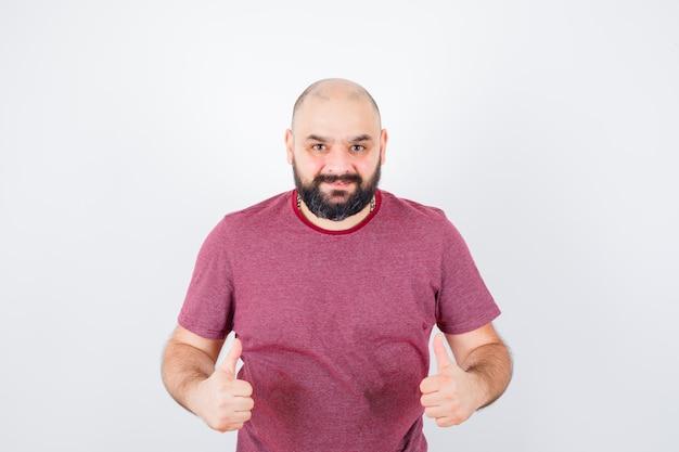 Jeune homme en t-shirt rose montrant le pouce vers le haut et l'air heureux, vue de face.