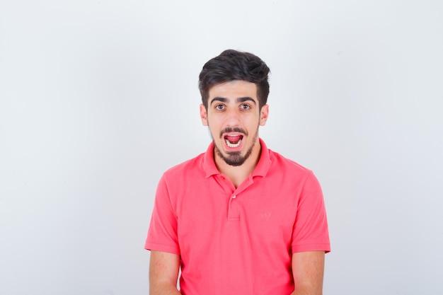 Jeune homme en t-shirt rose à la recherche et l'air étonné, vue de face.