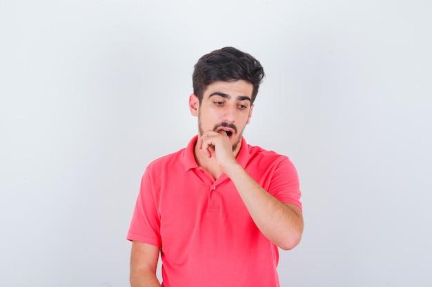 Jeune Homme En T-shirt Rose Tenant Le Doigt Dans La Bouche Et à L'aise, Vue De Face. Photo gratuit