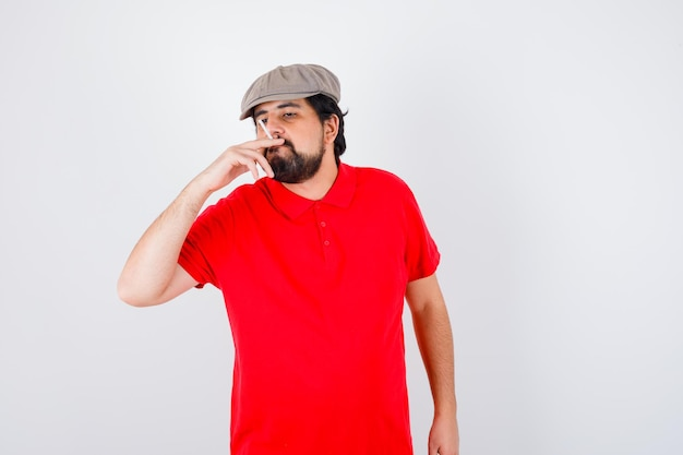 Jeune homme en t-shirt rouge, casquette fumeur, vue de face.