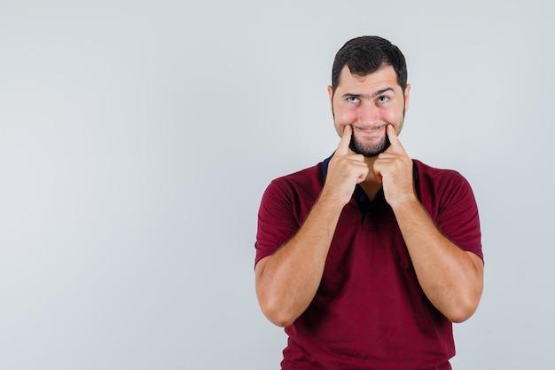 Jeune homme en t-shirt rouge pointant sur sa bouche et regardant drôle, vue de face.