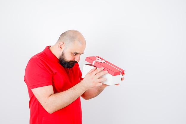 Jeune homme en t-shirt rouge regardant dans une boîte-cadeau et se demandant, vue de face.