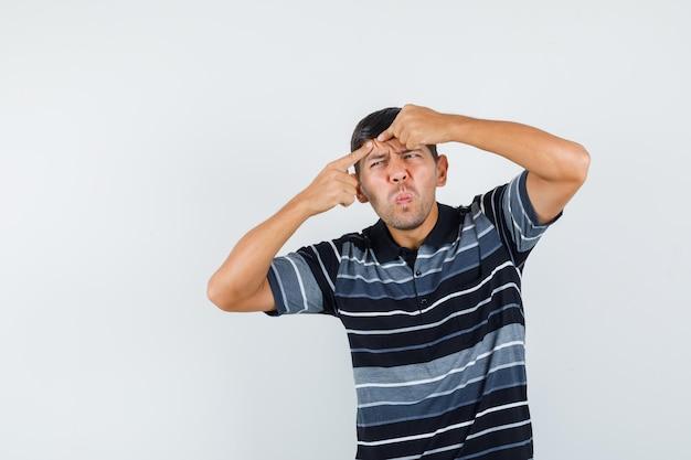 Jeune homme en t-shirt serrant son bouton sur le front, vue de face.