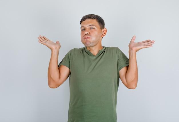 Jeune homme en t-shirt vert armée montrant un geste impuissant avec des joues qui soufflent, vue de face.