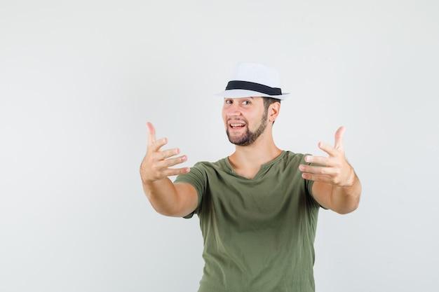 Jeune homme en t-shirt vert et chapeau invitant à venir et à la bonne humeur