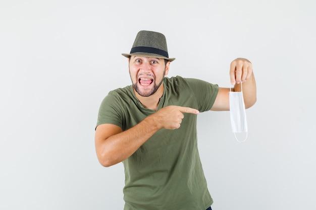 Jeune homme en t-shirt vert et chapeau pointant sur un masque médical