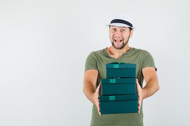 Jeune homme en t-shirt vert et chapeau présentant des coffrets cadeaux et à la joie