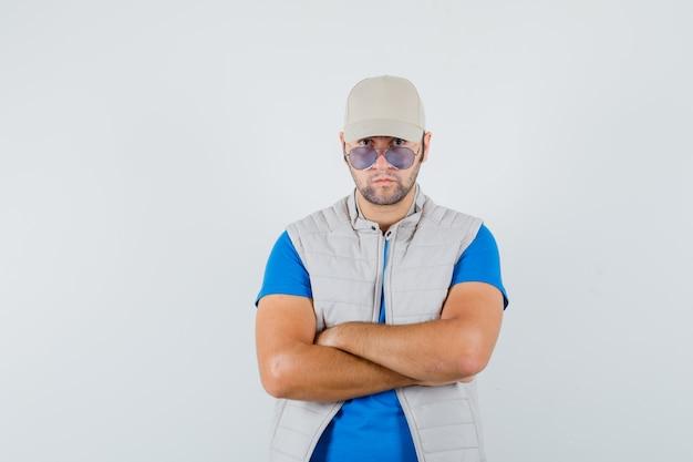 Jeune homme en t-shirt, veste, casquette debout avec les bras croisés et regardant confiant, vue de face.