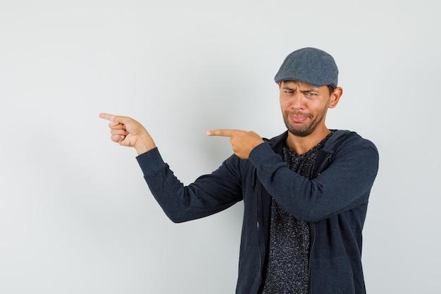 Jeune homme en t-shirt, veste, casquette pointant les doigts sur le côté et à la triste, vue de face.