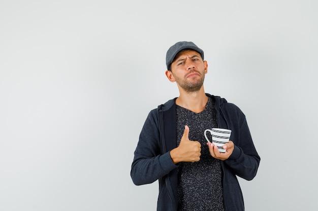 Jeune homme en t-shirt, veste, casquette tenant une tasse de boisson, montrant le pouce vers le haut, vue de face.