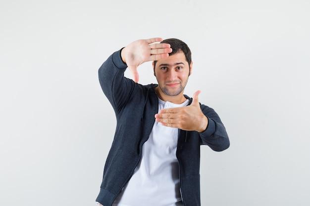 Jeune homme en t-shirt, veste faisant le geste du cadre et à la vue de face, heureux.
