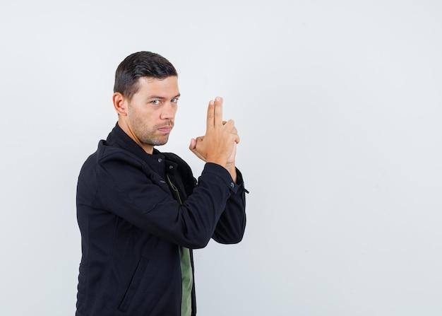 Jeune homme en t-shirt, veste montrant le geste du pistolet et semblant sérieux, vue de face.