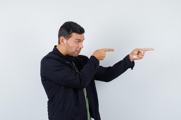 Jeune homme en t-shirt, veste pointant sur le côté et l'air concentré, vue de face.