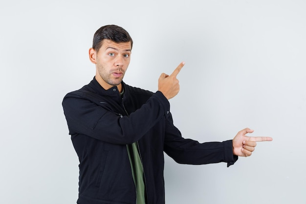 Jeune homme en t-shirt, veste pointant les doigts sur le côté et vers le haut et l'air confus, vue de face.
