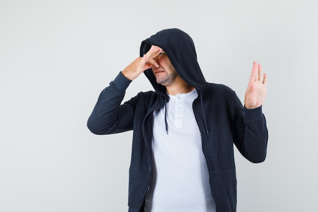 Jeune homme en t-shirt, veste se pinçant le nez en raison d'une mauvaise odeur et à la dégoûté, vue de face.