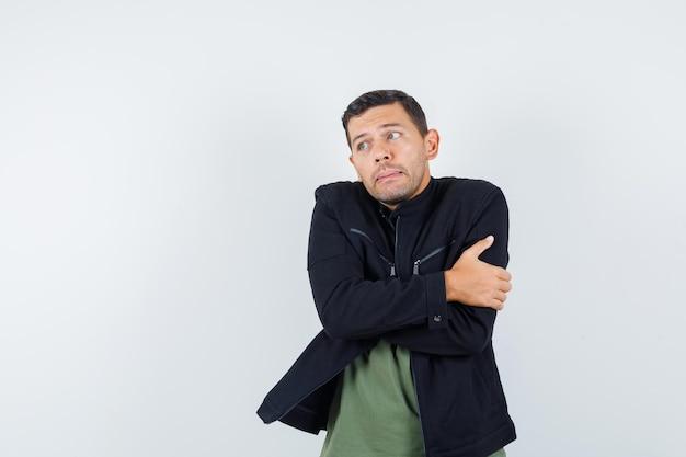 Jeune homme en t-shirt, veste se serrant dans ses bras et se sentant froid, vue de face.