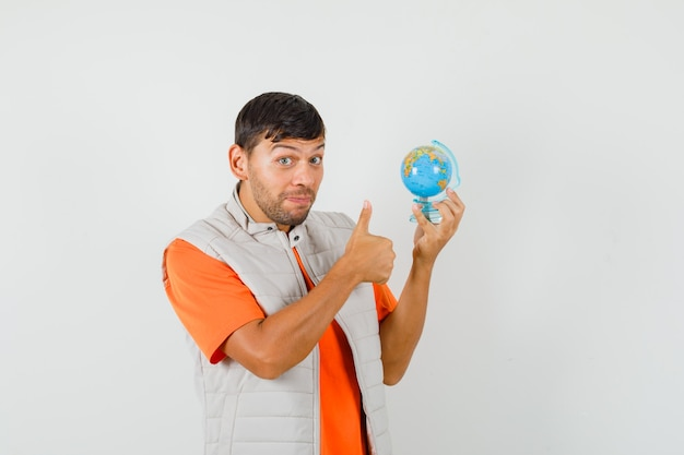 Jeune homme en t-shirt, veste tenant le globe de l'école, montrant le pouce vers le haut et à la joyeuse vue de face.