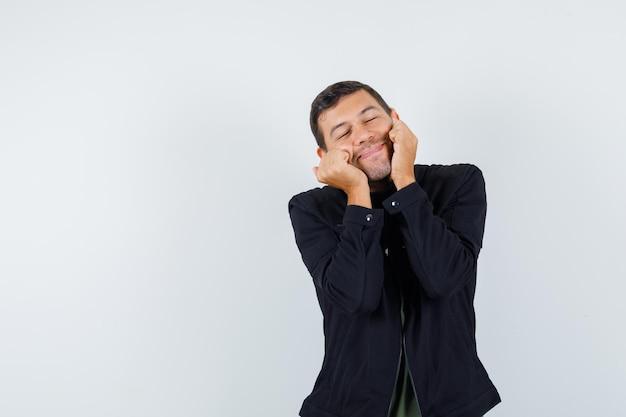 Jeune homme en t-shirt, veste tenant les poings sur les joues et l'air paisible, vue de face.