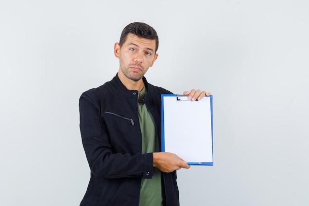 Jeune homme en t-shirt, veste tenant le presse-papiers et semblant sensible, vue de face.