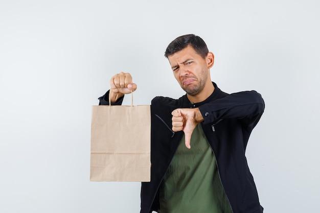 Jeune homme en t-shirt, veste tenant un sac en papier avec le pouce vers le bas et l'air mécontent, vue de face.