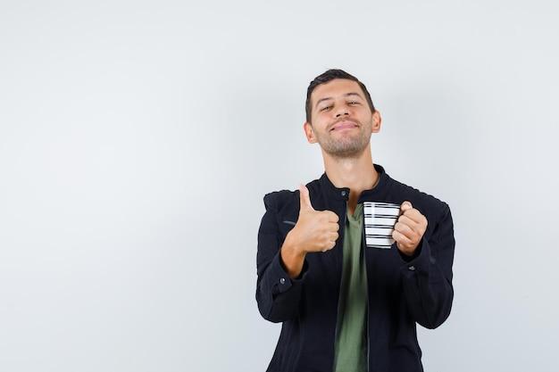 Jeune homme en t-shirt, veste tenant une tasse de boisson avec le pouce vers le haut et l'air joyeux, vue de face.