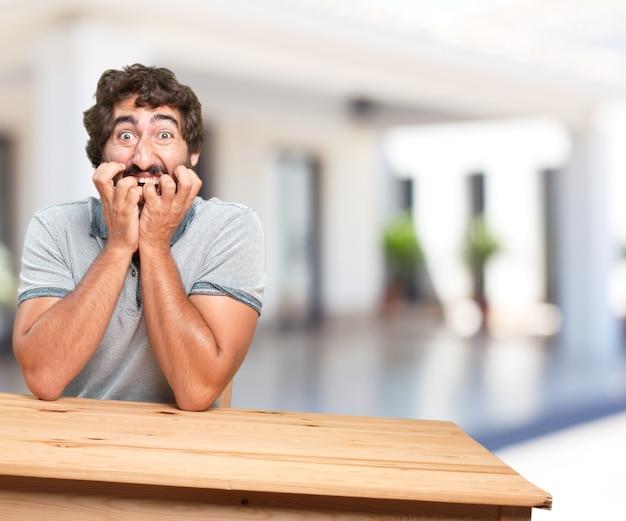 Jeune homme sur une table. expression inquiète