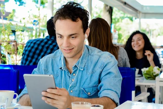 Jeune homme avec une tablette dans un café.