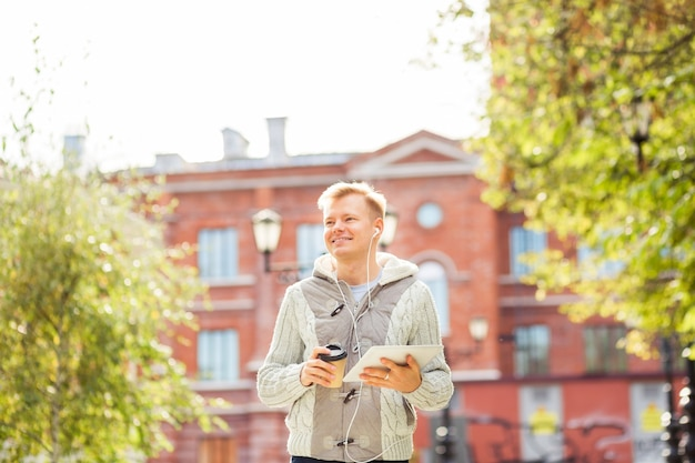 Jeune homme avec une tablette lisant des nouvelles à l'automne avec une tasse de café en papier