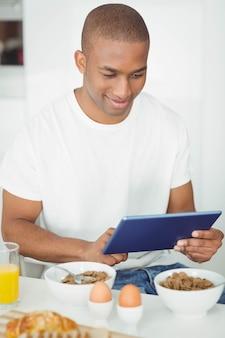Jeune homme avec tablette et petit déjeuner dans la cuisine à la maison