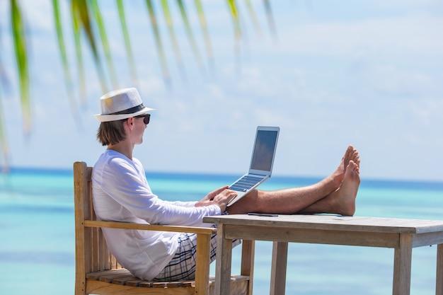 Jeune homme avec une tablette tactile pendant les vacances à la plage tropicale