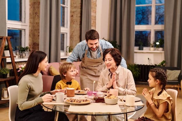 Jeune homme en tablier penché sur une table servie avec un gâteau glacé fait maison avec une bougie allumée parmi sa famille pendant le dîner de fête