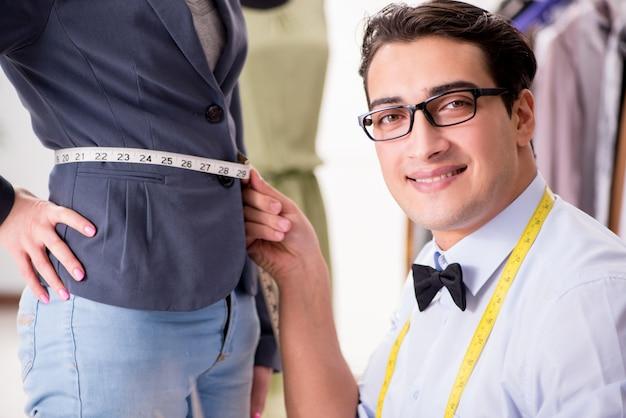 Jeune homme tailleur travaillant avec une cliente