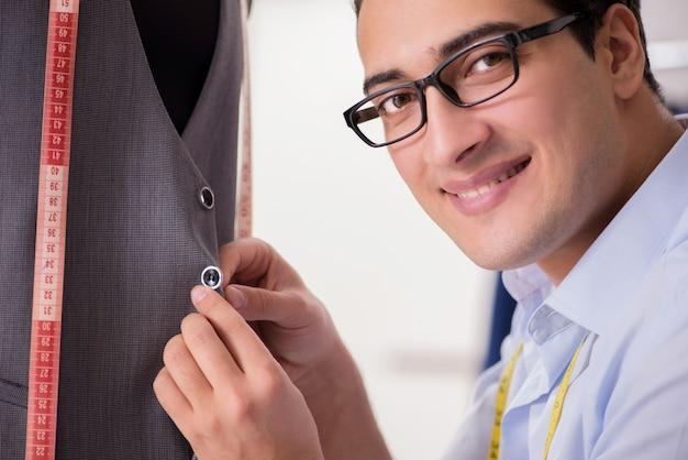 Jeune homme tailleur travaillant sur de nouveaux vêtements
