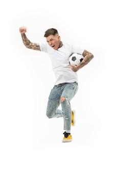 Le jeune homme en tant que joueur de football soccer botter le ballon au studio