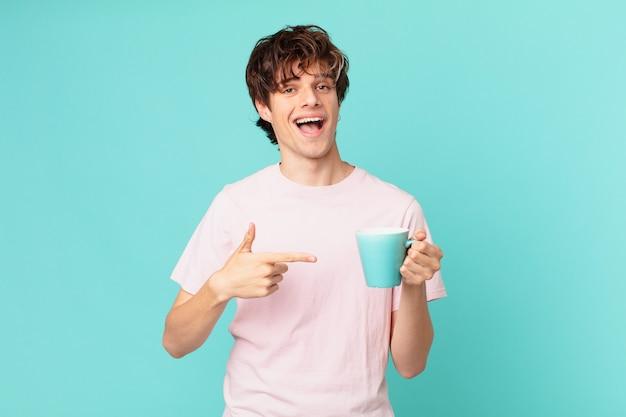 Jeune homme avec une tasse de café à l'air excité et surpris en pointant sur le côté