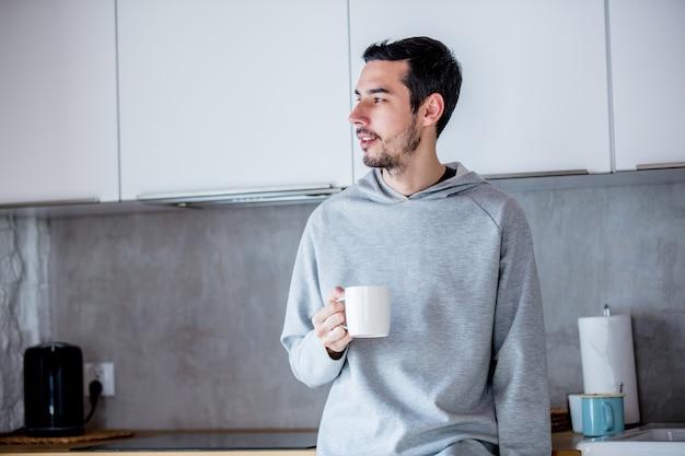 Jeune homme avec une tasse de café rester à la cuisine à la maison
