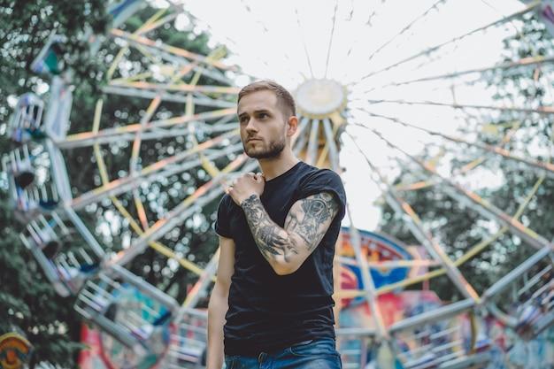 Jeune homme tatoué dans un parc d'attractions sur le fond d'un manège