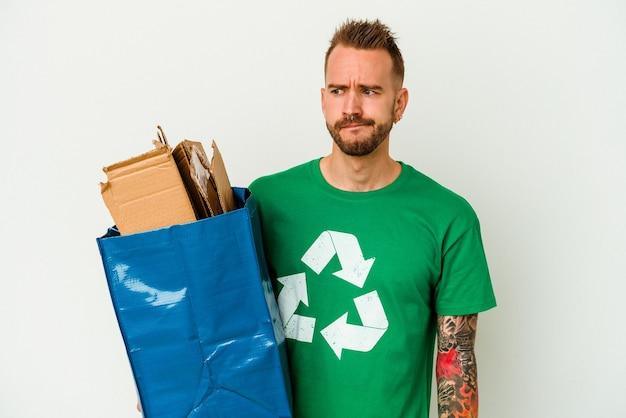 Jeune homme tatoué de race blanche en carton recyclé isolé sur fond blanc confus, se sent douteux et incertain.