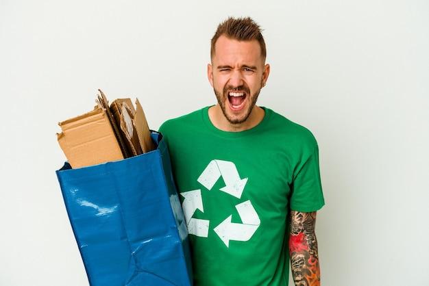 Jeune homme tatoué de race blanche en carton recyclé isolé sur fond blanc criant très en colère et agressif.