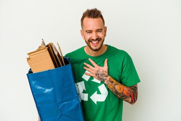 Jeune homme tatoué de race blanche en carton recyclé isolé sur fond blanc éclate de rire en gardant la main sur la poitrine.