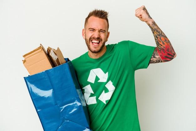 Jeune homme tatoué de race blanche en carton recyclé isolé sur fond blanc levant le poing après une victoire, concept gagnant.