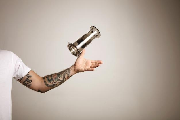 Un jeune homme tatoué en t-shirt blanc attraper un aeropress gris vide sur mur gris clair