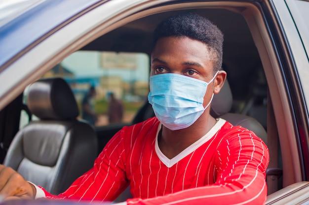 Jeune homme de taxi africain conduisant alors qu'il utilise un masque facial pour prévenir, prévenir, s'empêcher de l'épidémie dans la société