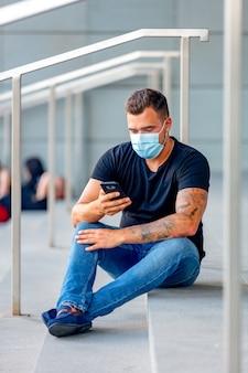 Jeune homme avec téléphone portable sur les marches du campus universitaire