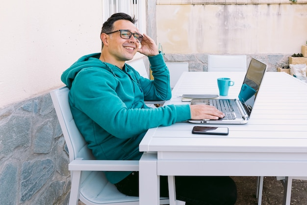 Jeune homme télétravaillant, pensant, tapant sur son ordinateur portable dans le jardin de sa maison