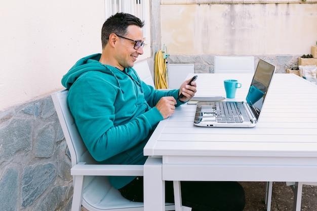 Jeune homme télétravaillant avec son ordinateur portable, regardant son téléphone portable, dans le jardin de sa maison