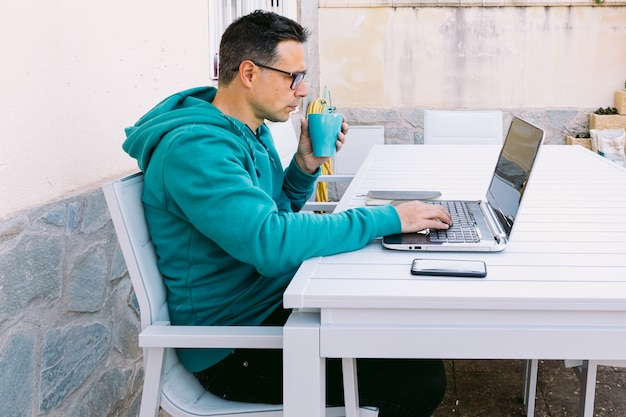 Jeune homme télétravaillant avec son ordinateur portable, tapant sur le clavier, dans le jardin de sa maison